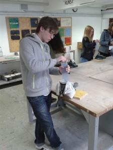 Julien (15) glättet die Kanten einer Acrylglasplatte 1