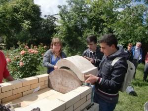Michelle aus Deutschland und Nicola aus Italien setzen gemeinsam das erste Bogenstück auf den Ofen HP