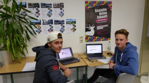 Max und Jan präsentieren am PC ihre Sieger-Logos HP