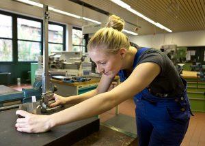 Eine Technische Assistentin im Praxisunterricht in der CNC-Werkstatt